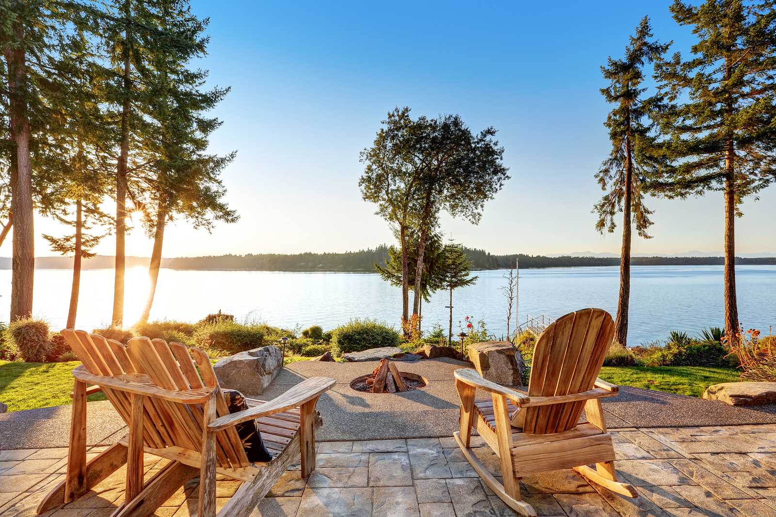 Back yard of waterfront house with adirondack chairs and fire pit. Beautiful water view at sunset. Northwest USA