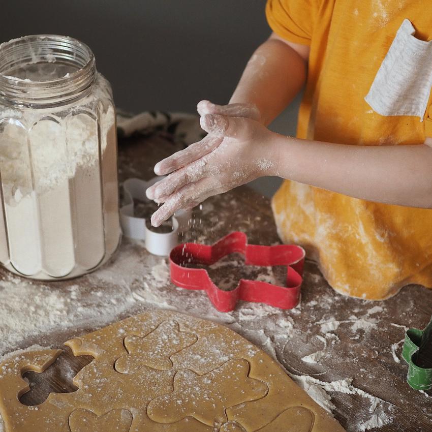 Child in an orange shirt making gingerbread men