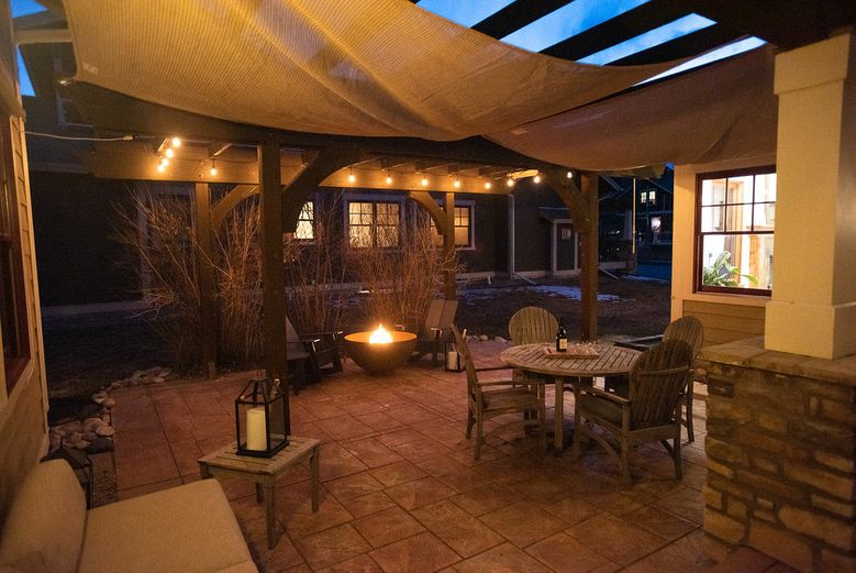 Outdoor patio at twilight with lights and firepit