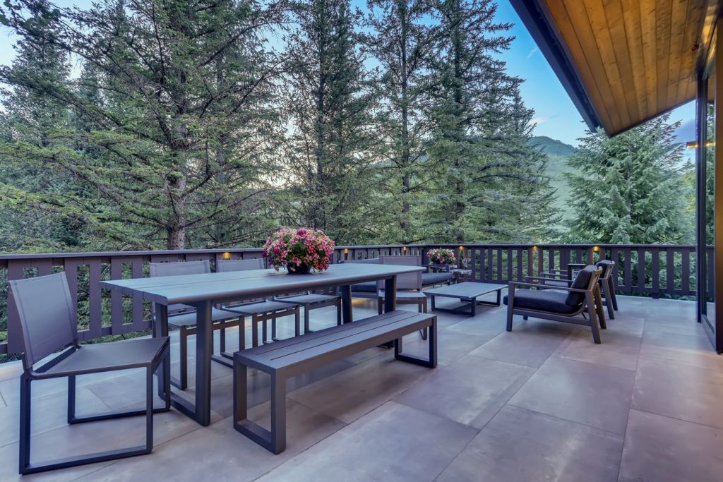 Prepping your home for sale - large outdoor patio with furniture among the trees