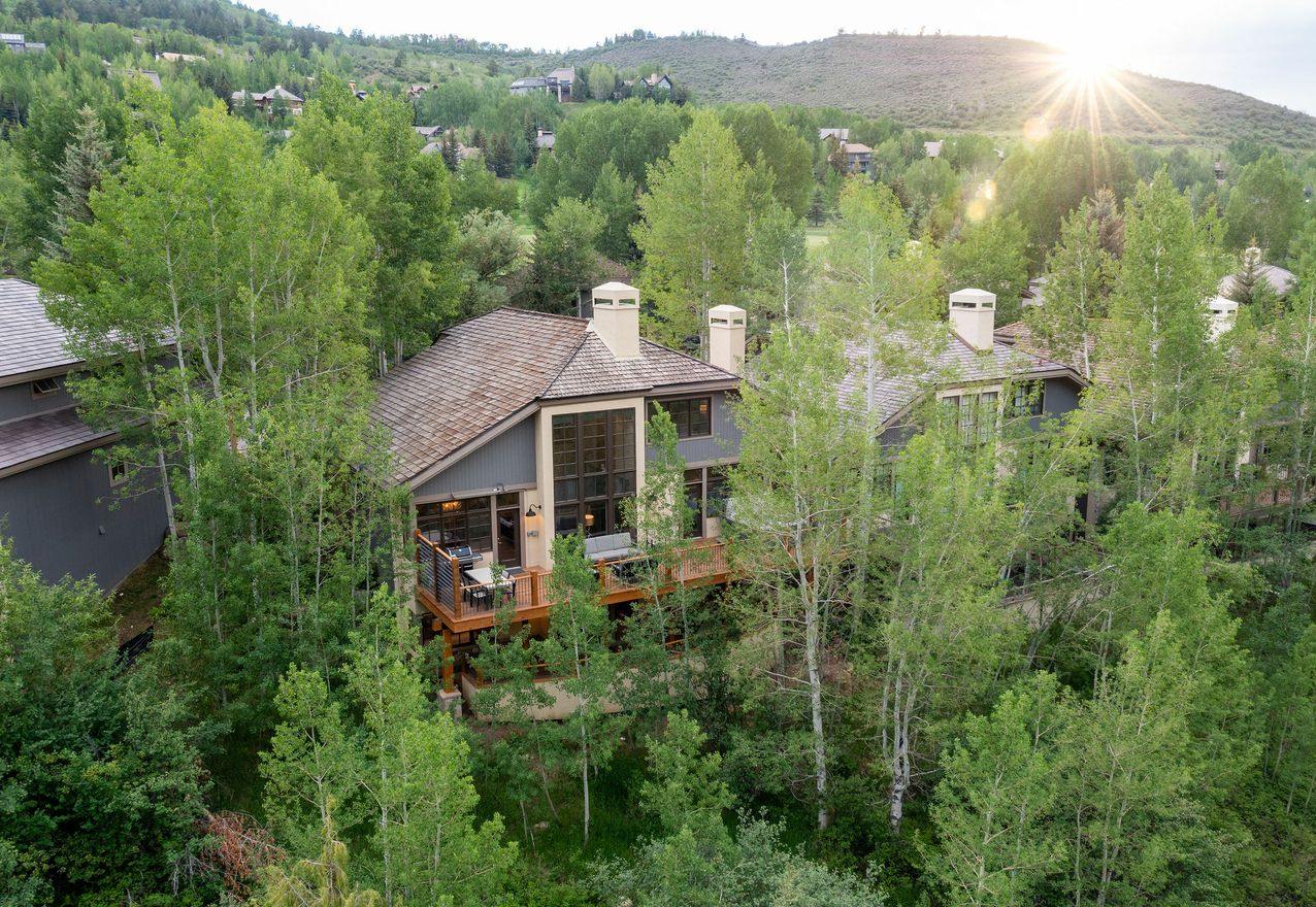 Summer exterior of luxury mountain home tucked away in the aspens.