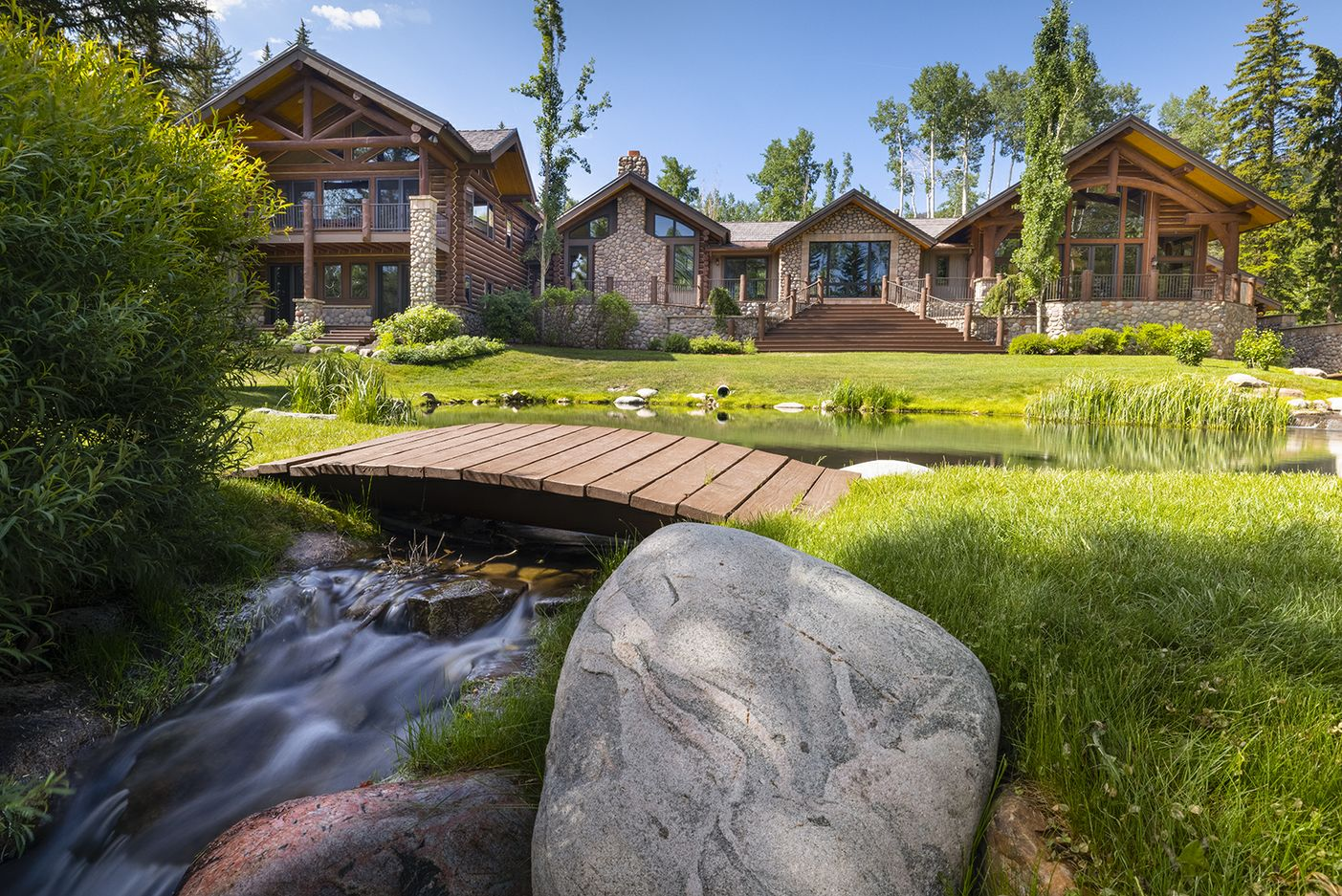 Summer exterior image of luxury mountain home with stream and a manicured lawn