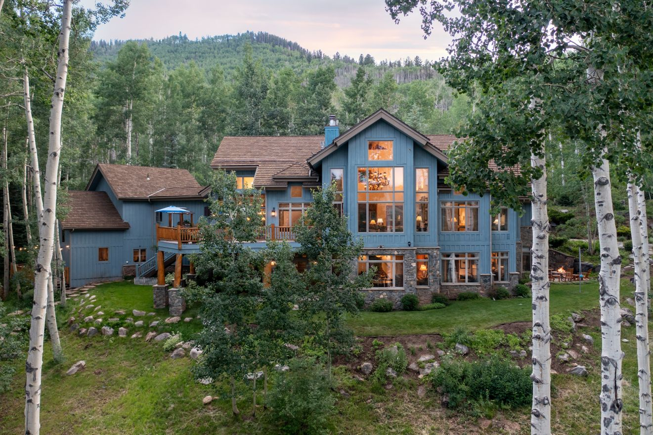 Summer exterior image of a mountain luxury home nestled in a forest of aspens
