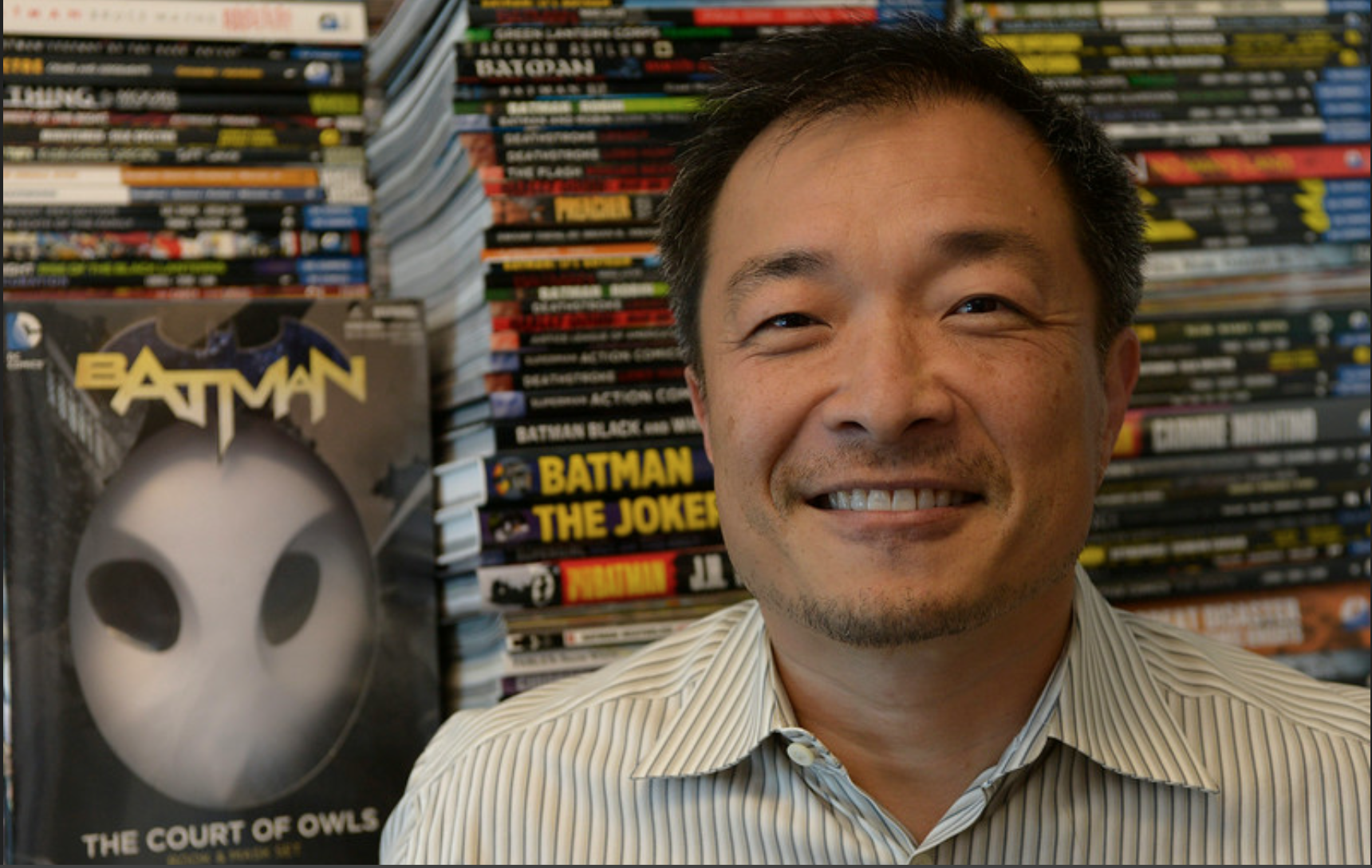 Jim Lee poses with Batman Merchandise in the background of his office.