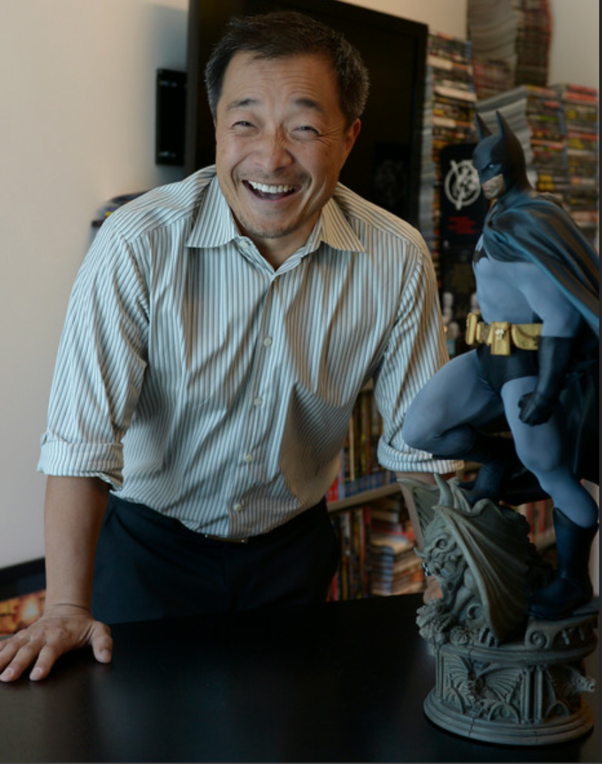 Jim Lee smiles in his offices next to a Batman Statue