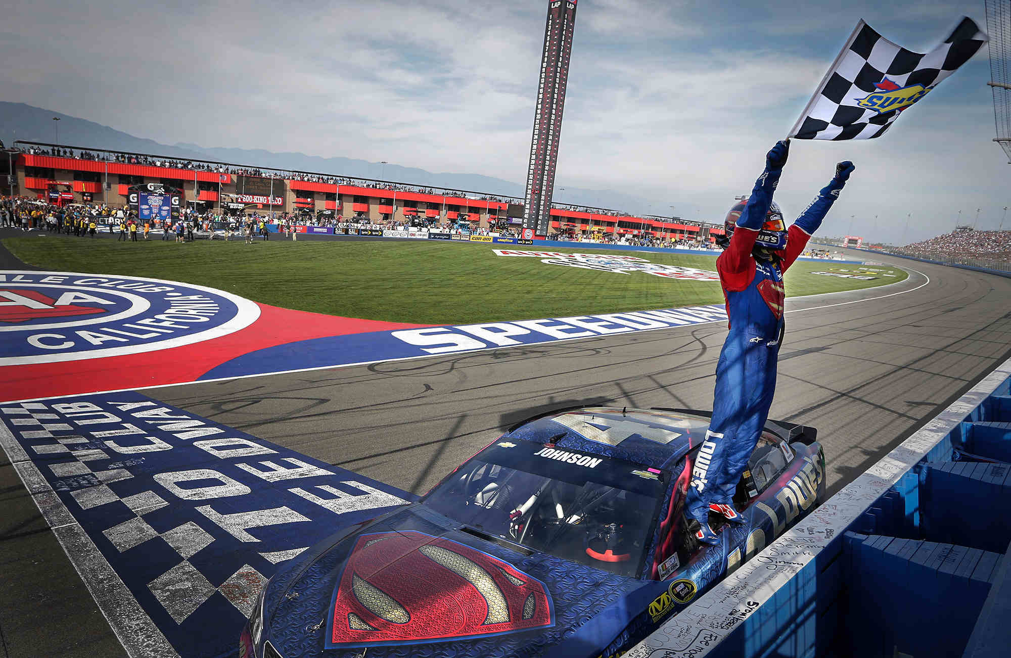 Jimmie Johnson, driver of the #48 LoweÕs/Superman Chevrolet SS, celebrates his 77th career victory with a wave of the checkered flag Sunday, March 20, 2016 in the NASCAR Sprint Cup Series race at Auto Club Speedway in Fontana, California. (Photo by Garry Eller for Chevy Racing)