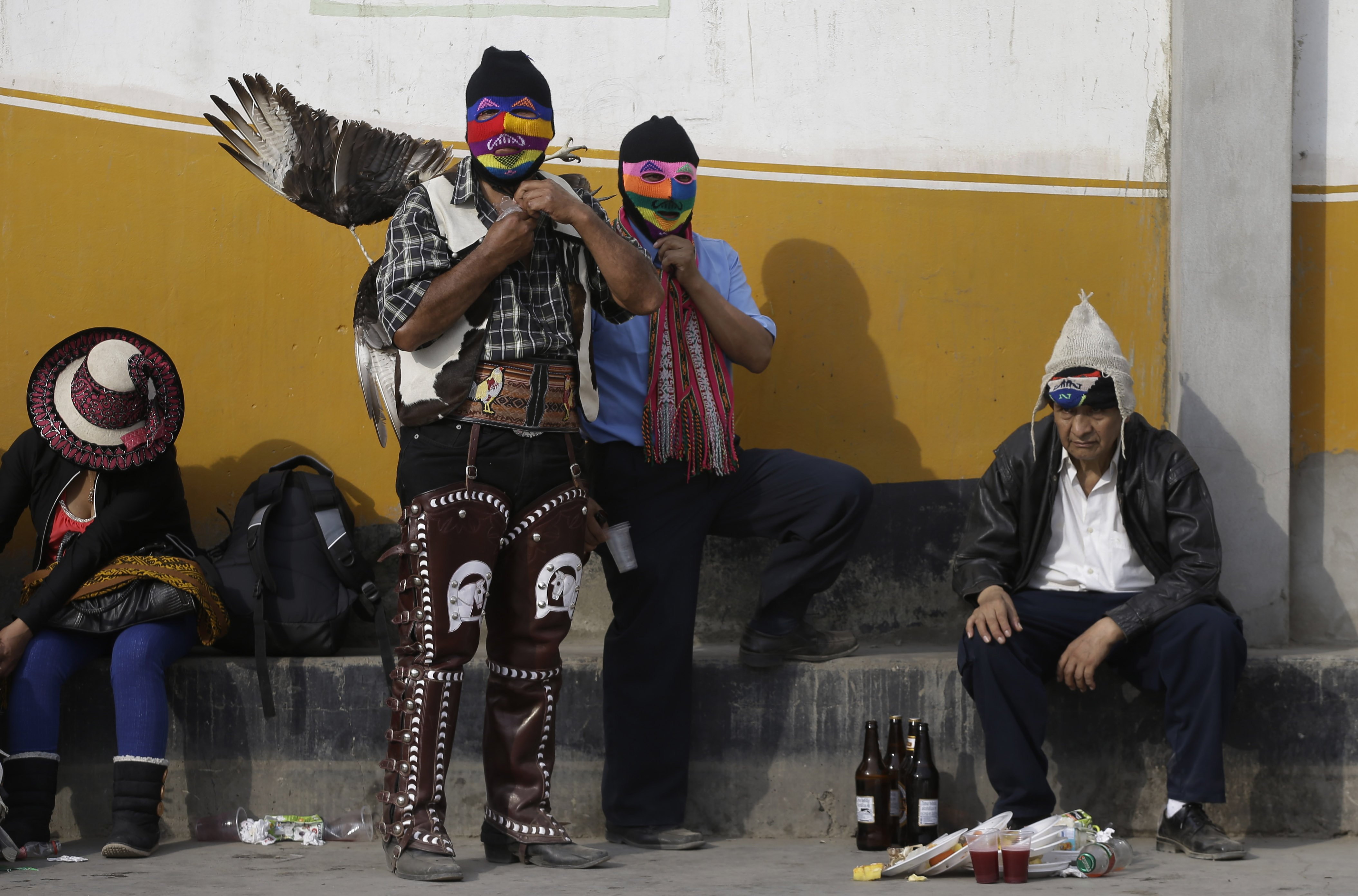 "In this Dec. 25, 2015 photo, masked fighters put on their costumes for the ""Takanakuy"" ritual fighting event on the outskirts of Lima, Peru on Christmas day, with the winged fighter wearing leg guards used by horseriders, to protect him from kicks to the legs. ""Takanakuy"" in the Quechua language roughly means to ""beat each other up,"" and has its roots in pre-Hispanic and even pre-Incan Andean traditions. (AP Photo/Martin Mejia)"