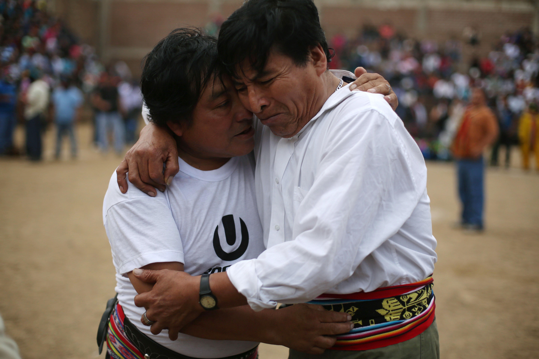 """En esta imagen, tomada el 25 de diciembre de 2015, Nestor Gabina (izquierda) abraza a su vecino Gabriel Anaya tras pelear en el """"Takanakuy"""", una lucha ritual, en las afueras de Lima, en Perú, en el día de Navidad. Los dos hombres, vecinos de hace más de 20 años, se agarran a golpes por los límites de sus tierras, una disputa que inclusive ha llegado mutuas denuncias judiciales. La pelea dura sólo unos minutos y el referí Neto Mendoza los separa sin proclamar un ganador oficial. Los hombres se abrazan y rompen en llanto. La mezcla de adrenalina y pena que los invade es calmada con más cerveza. (Foto AP/Martin Mejia)"""