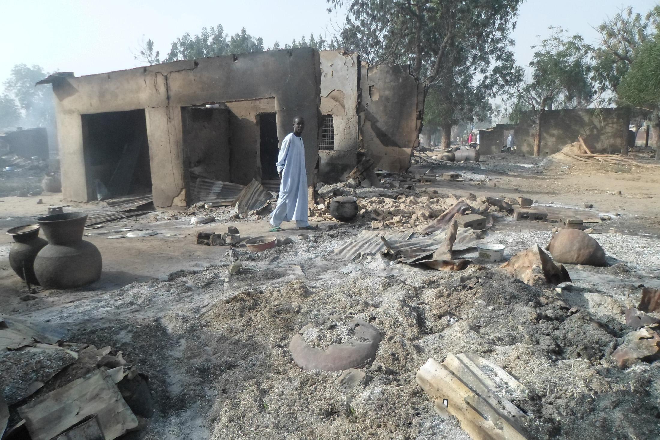 Un hombre camina entre viviendas quemadas luego de un ataque de extremistas de Boko Haram en al pueblo de Dalori, a 5 kilómetros (3 millas) de Maiduguri, Nigeria, el domingo 31 de enero de 2016. (Foto AP/Jossy Ola)