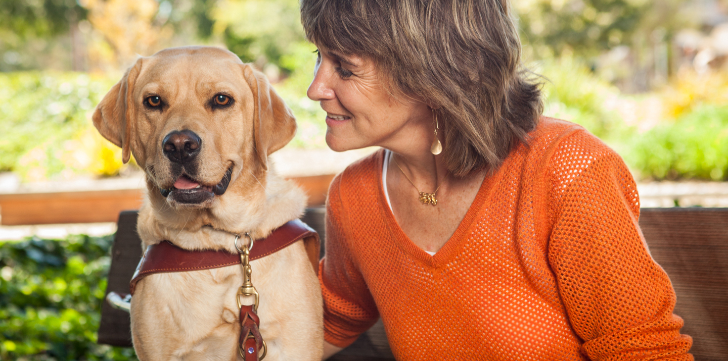 A female GDB graduate smiles while looking at her yellow Lab guide dog