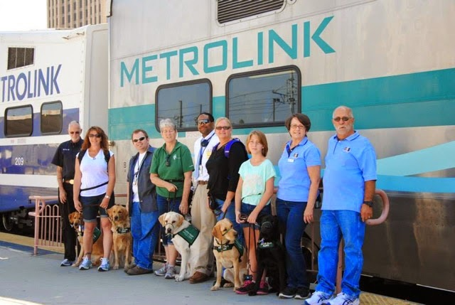 Puppy raisers pose in front of the MetroLink train.