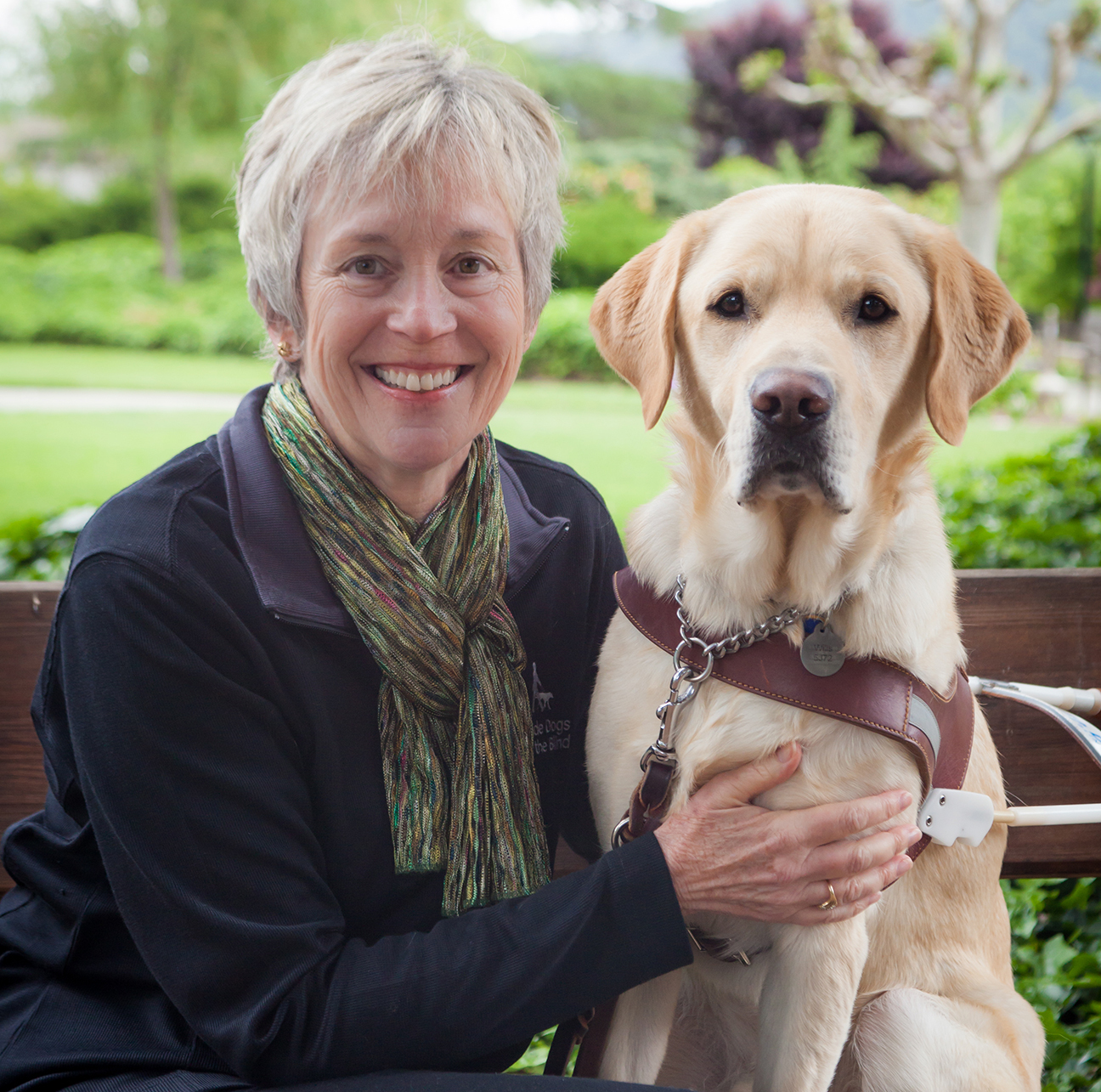 Joan poses on a bench, at our San Rafael campus, with her arm around a Yellow Lab guide dog in harness.