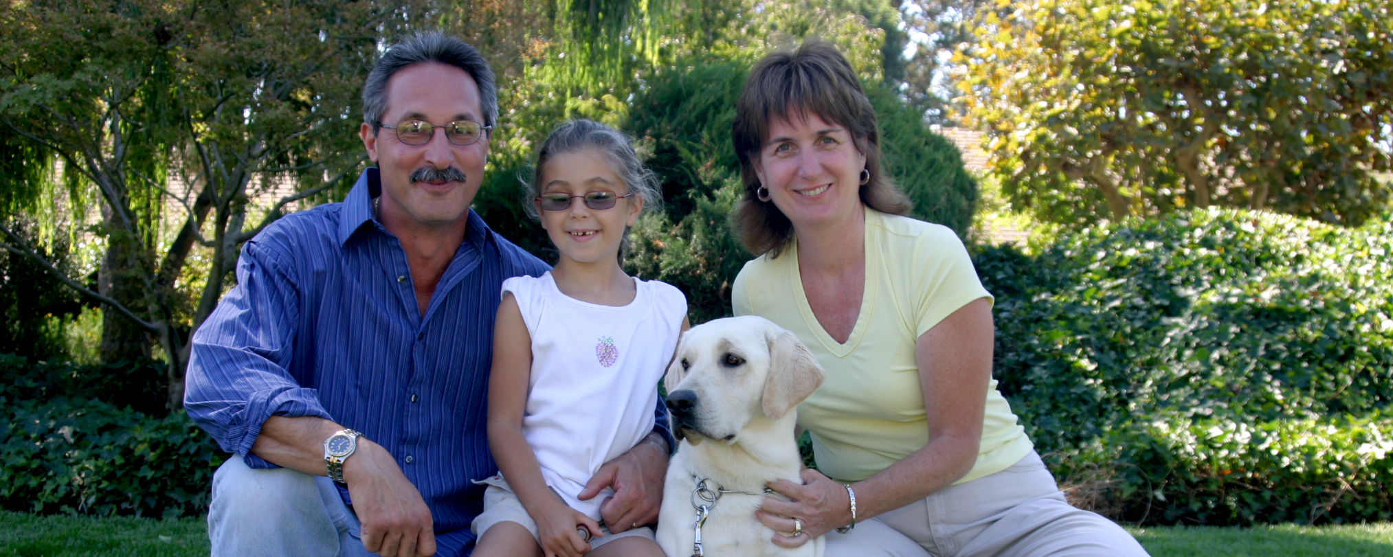 Parents with their young daughter in the middle (wearing glasses) sit smiling with a yellow Lab