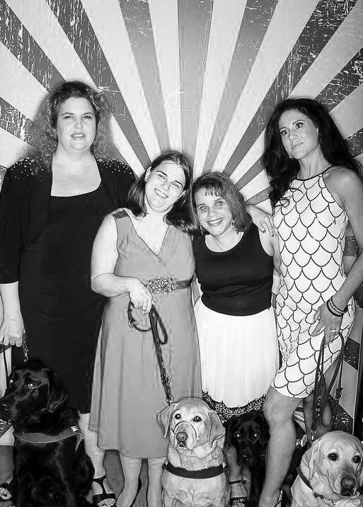 Four members of Mommies with Guides pose at the GDB Pinot and Pups Gala