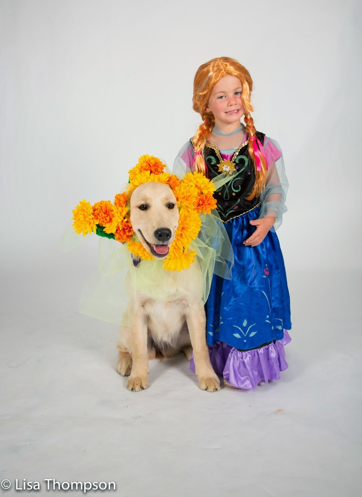 Guide dog puppy Marigold wears a yellow and orange flower wreath on her head. A young girl in a princess costume is next to Marigold.