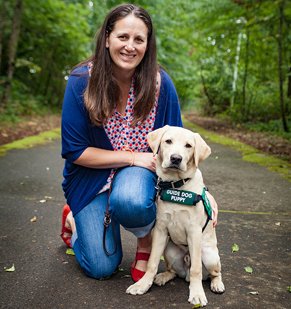 Megan, kneels with a Yellow Lab guide dog puppy in training wearing its green puppy coat.