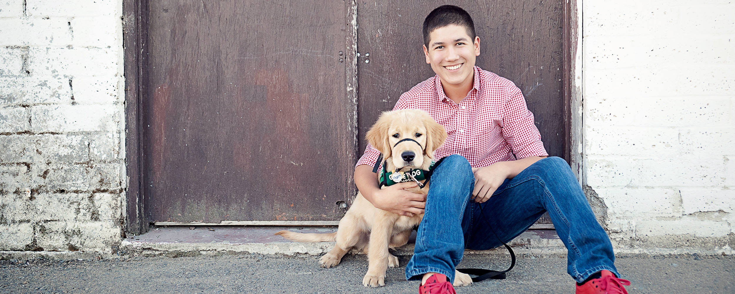 A teenage male puppy raiser smiles while sitting with his young Golden Retriever guide dog puppy