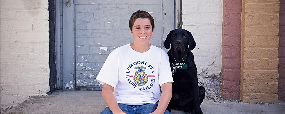 A teenage puppy raiser with his black Lab puppy.
