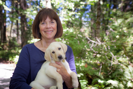 Ruth Ann Dodson holding a yellow Lab puppy.