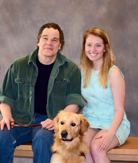 GDB Grad Keith Gillard and Puppy Raiser Sierra Hayes sit side by side with Keith's guide Golden Retriever Newburg