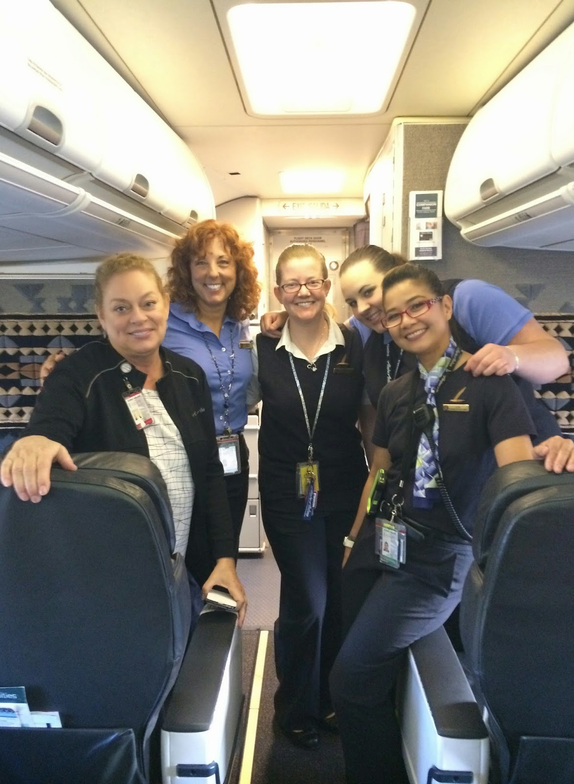 Five Alaska Airlines flight attendants smile for a group photo on the plane.