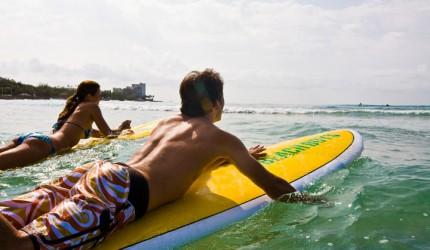 Couple going surfing off Waikiki Beach | Hawaii Tourism Authority (HTA) / Tor Johnson