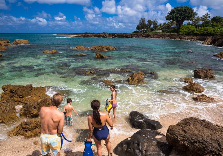 Family on the beach to snorkel a North Shore cove.  | Hawaii Tourism Authority (HTA) / Tor Johnson
