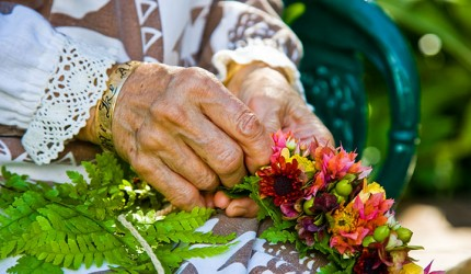 Aunty Amelia Bailey creating a beautiful haku lei. Photo courtesy of Hawaii Tourism Authority (HTA) / Tor Johnson.