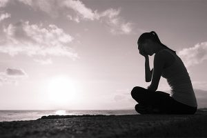 Photo of a stress out woman in front of sunset