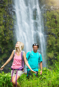 Couple having fun together outdoors on hike to amazing waterfall in Hawaii.