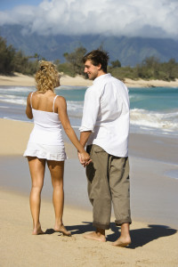 Attractive couple holding hands and smiling at eachother walking on Maui, Hawaii beach.
