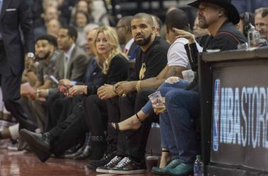 Canadian recording artist Drake watches the action during the first quarter in a game between the Golden State Warriors and the Toronto Raptors at Air Canada Centre.