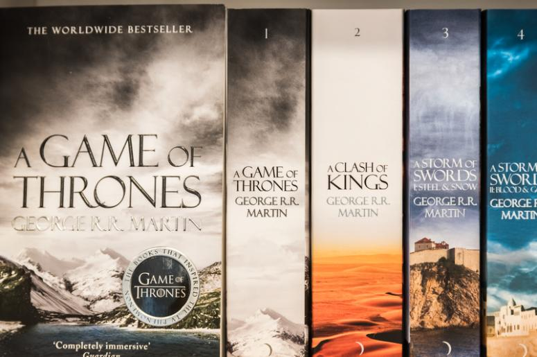 BUCHAREST, ROMANIA - MARCH 07, 2015: Game Of Thrones Books For Sale On Library Shelf. It is the first novel in a series of high fantasy novels by American author George R. R. Martin.