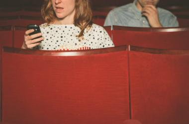 Woman using her phone in a theater while a young man sitting behind her look on.
