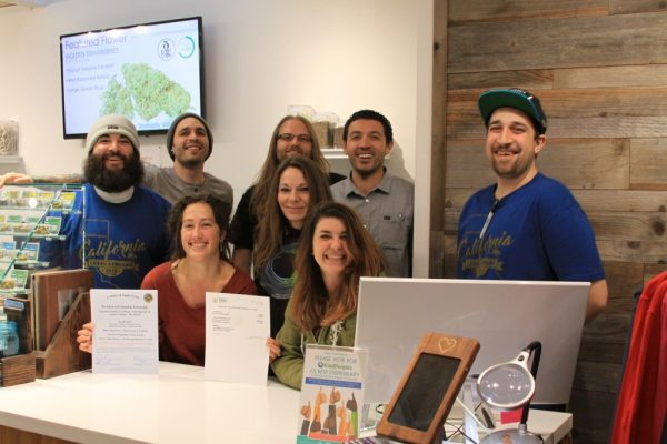 KindPeoples staff pase in front of some of the first state licenses to sell cannabis in history.
