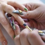 Christina Blea paints on ground up cannabis onto the nails of writer Emily Earlenbaugh, in Christina's Dabulous Nail Bar, at her home in Richmond, Calif., on Wednesday January 31, 2018.
