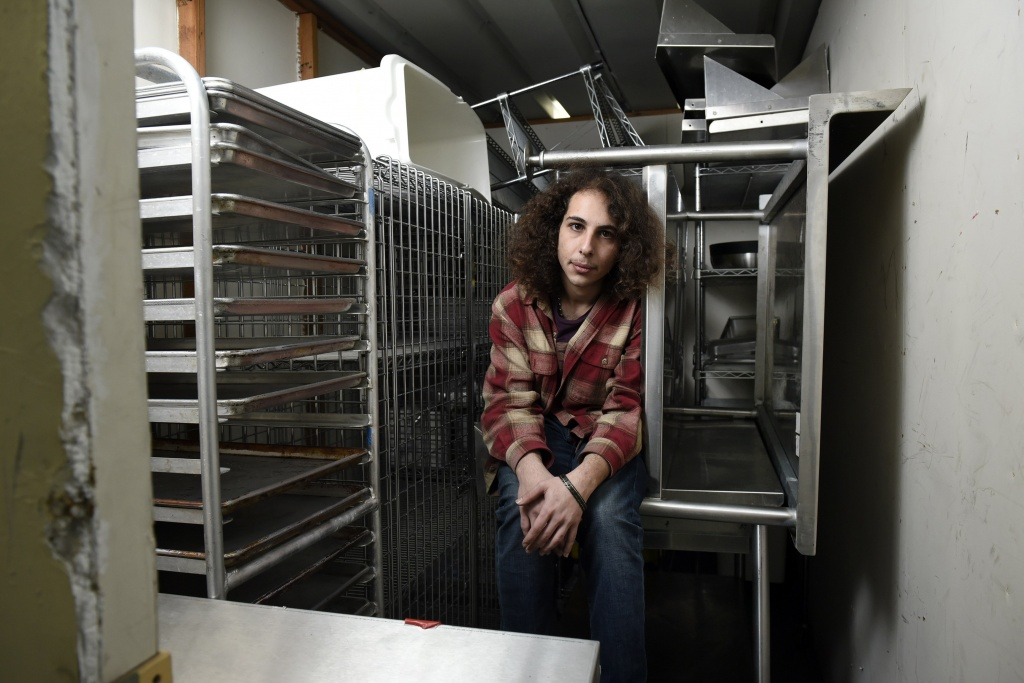 Brian Edwards sits in a storage space among stored kitchen equipment that was used to produce his Higherveda Medicinals edibles line, in San Leandro, Calif. | Photo: Michael Short
