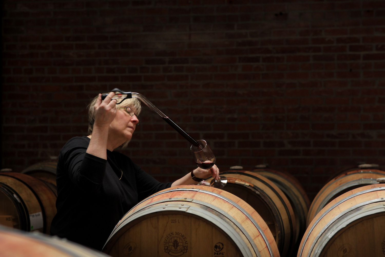Urban Legend, Urban Legend Winery, Oakland, Oakland winery, Oakland tasting room, wine tasting, woman taking wine out of a barrel, Oakland, California, The Press