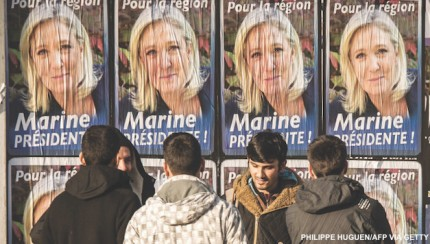 Migrant men stand in front of electoral posters of French far-right National Front (FN) party President Marine Le Pen in Calais on December 7, 2015. France's far-right National Front saw record-high results in the first round of regional polls on December 6, held under a state of emergency just three weeks after Islamic extremists killed 130 people in Paris. / AFP / PHILIPPE HUGUEN        (Photo credit should read PHILIPPE HUGUEN/AFP/Getty Images)