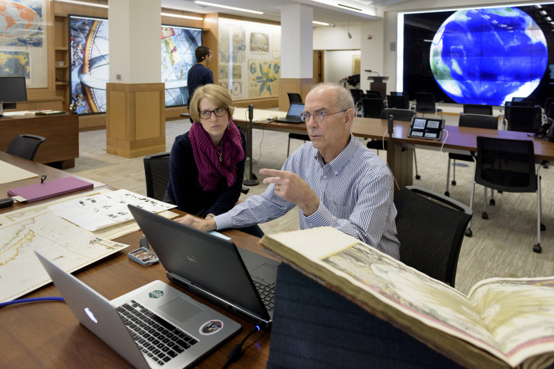 cartographic specialist and donor of the maps working at a desk covered with maps and computers