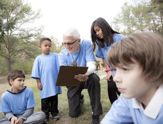 Older man coaching young children.