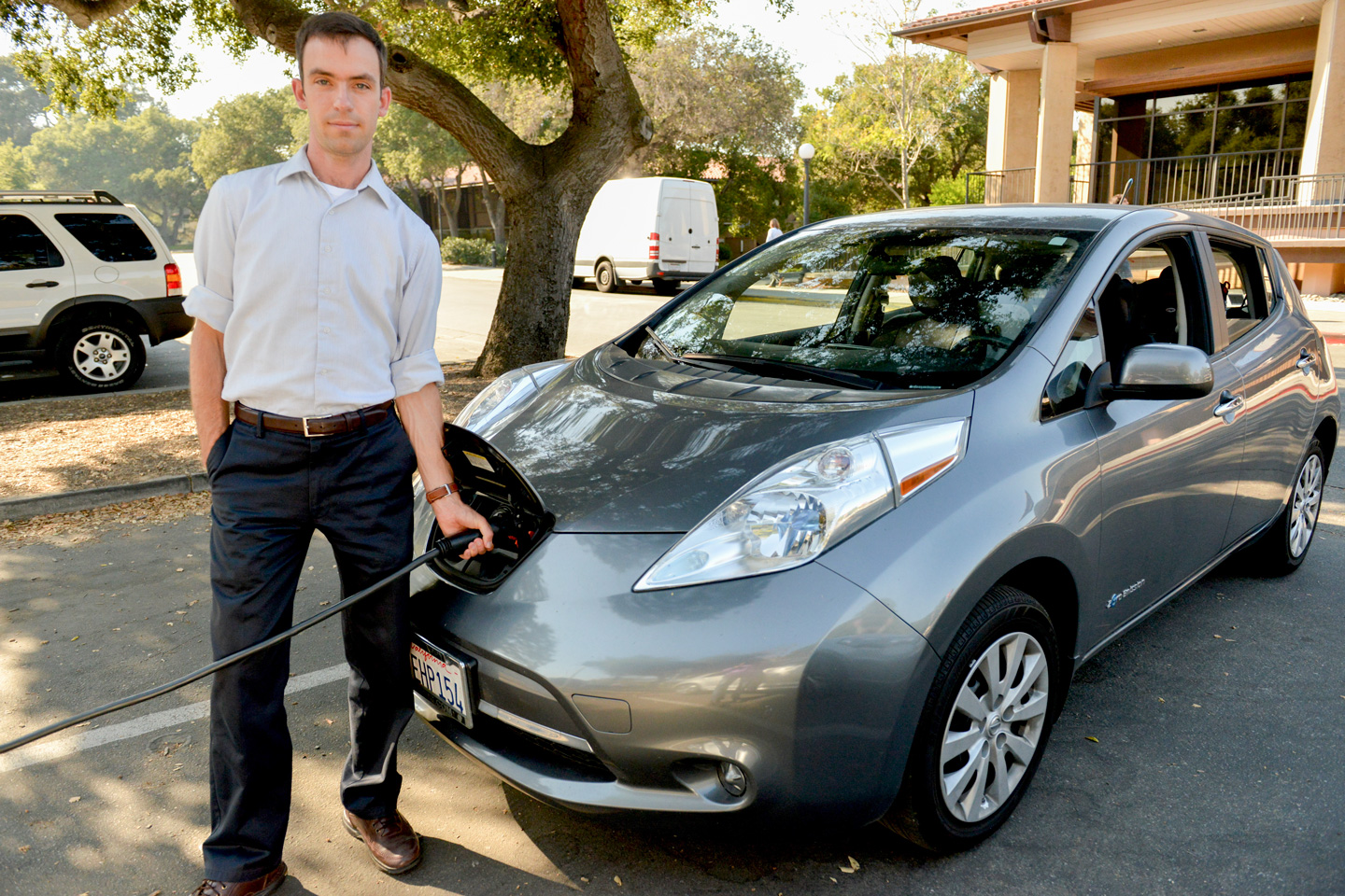 Researcher Matthew Pellow charges his all-electric Nissan Leaf at Stanford. Pellow has found that battery electric vehicles are a more cost-efficient choice for reducing carbon dioxide emissions than cars powered by hydrogen.
