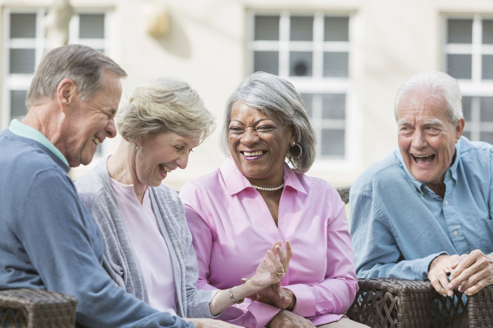 four multi-ethnic seniors sitting together outdoors, talking and laughing