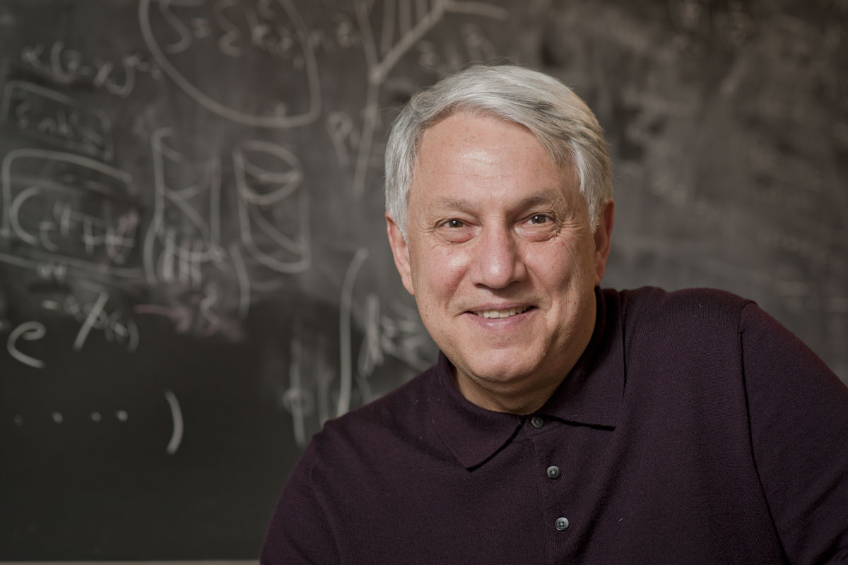 portrait of Andre Linde, professor of physics, in front of a blackboard of equations