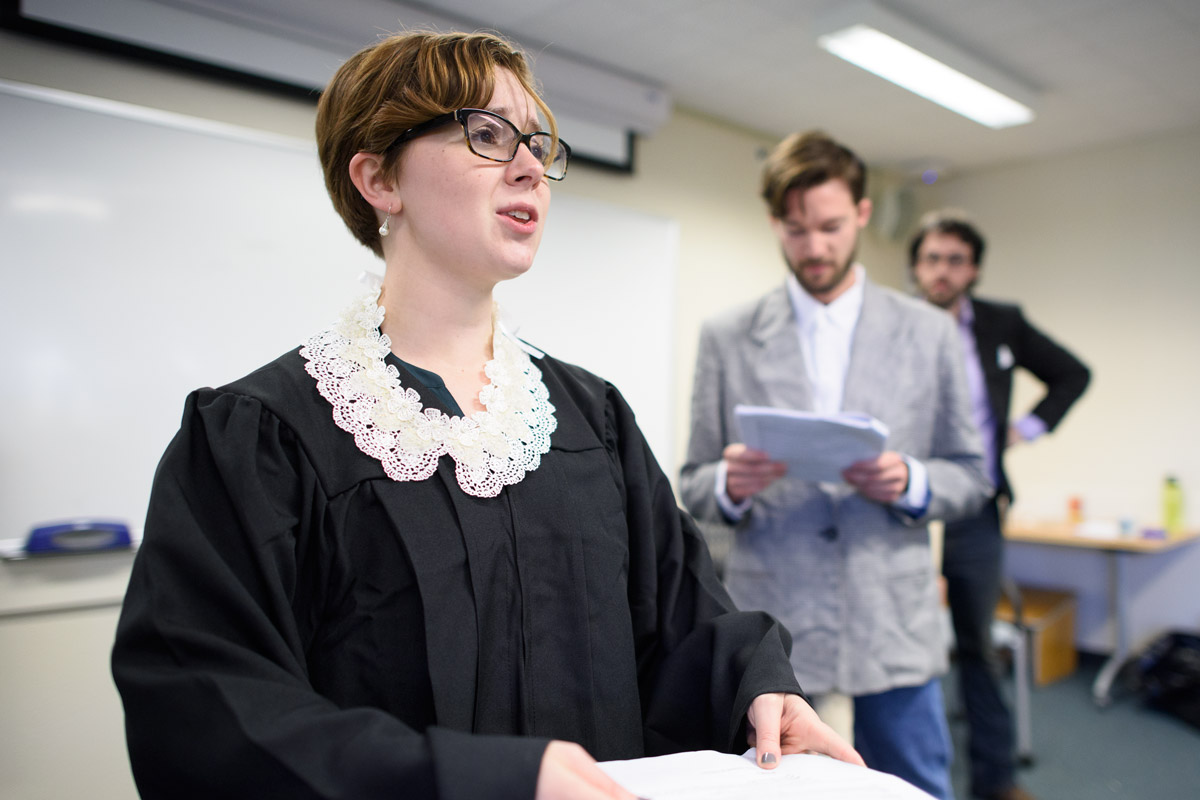Stanford graduate students in classics translated and adapted an ancient Greek play to lampoon modern politics. In this scene from rehearsal, Lizzy Ten-Hove portrays Supreme Court Justice Ruth Bader Ginsburg while David Pickel portrays political strategist Steve Bannon and Kilian Mallon plays Liberty University President Jerry Falwell Jr.