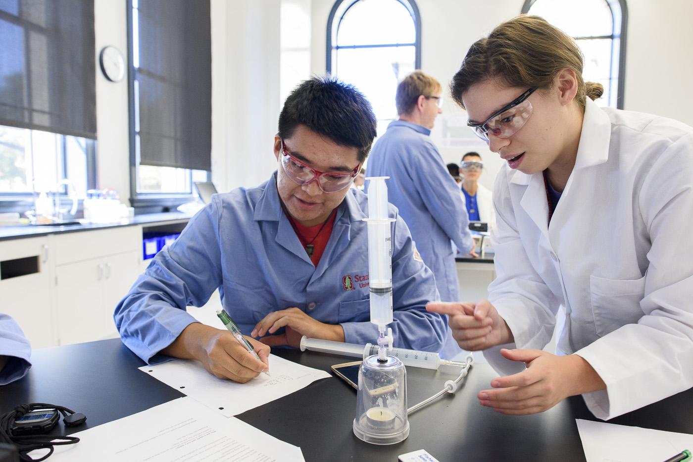 Leland Scholars Ely Jay Nez and Lizbeth Gomez observe changes in a lit candle after introducing nitrogen into a sealed jar.