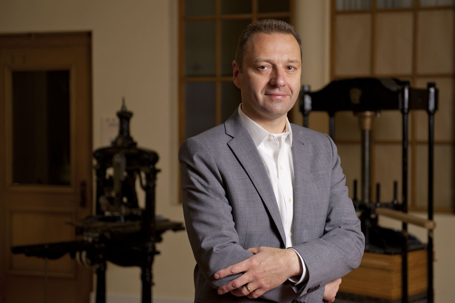 portrait of Alan Harvey, director of Stanford University Press, with old hand-operated printing presses in background