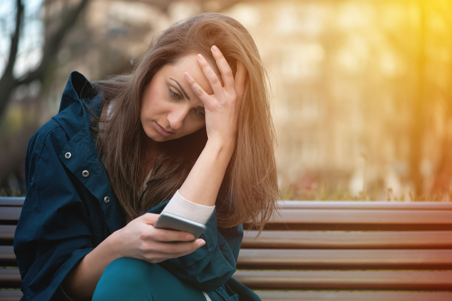 young woman on a bench looking at her cell phone