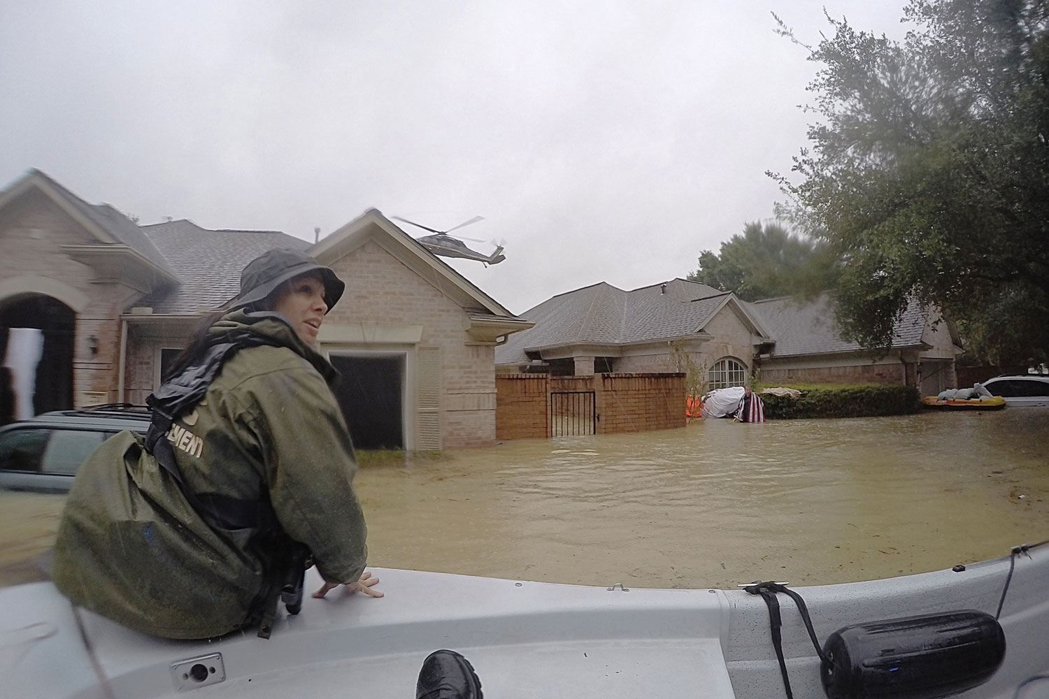 Neighborhood under water with guard in boat in foreground and helicopter flying overhead in background
