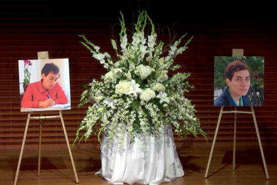 Two large photos of Maryam Mirzakhani with a flower arrangement on stage.